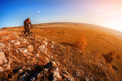 Cyclist Riding the Bike on the Mountain Rocky Trail at Sunset. Extreme Sports. Wide angle and fisheye. Cyclist in the helmet and with red backpack. Spring stock photography