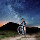 Cyclist riding bike in the night under starry sky Stock Photo