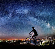 Cyclist riding bike in the night under starry sky Royalty Free Stock Photography