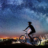 Cyclist riding bike in the night under starry sky Stock Photography