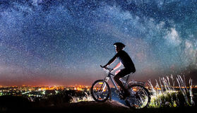 Cyclist riding bike in the night under starry sky Royalty Free Stock Images