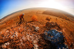 Cyclist riding a bike on an off road to the sunset. Wild landscape Stock Photos