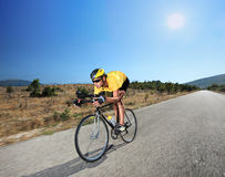 Cyclist riding a bike on an open road in Macedonia. With a sun in the background Stock Photo
