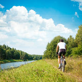 Cyclist Riding a Bike on River Bank royalty free stock images