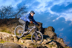 Cyclist Riding the Bike on the Rocky Trail at Sunset. Extreme Sport Concept. Space for Text. Royalty Free Stock Images