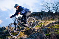 Cyclist Riding the Bike on the Rocky Trail at Sunset. Extreme Sport Concept. Space for Text. Royalty Free Stock Photo