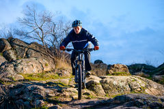 Cyclist Riding the Bike on the Rocky Trail at Sunset. Extreme Sport Concept. Space for Text. Royalty Free Stock Photos