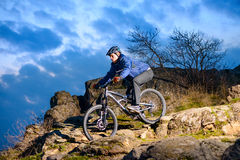 Cyclist Riding the Bike on the Rocky Trail at Sunset. Extreme Sport Concept. Space for Text. Stock Photos