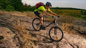 Cyclist Riding the Bike on Rocky Trail at Sunset. Extreme Sport and Enduro Biking Concept. stock photo