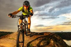 Cyclist Riding the Bike on Rocky Trail at Sunset. Extreme Sport and Enduro Biking Concept. royalty free stock photography