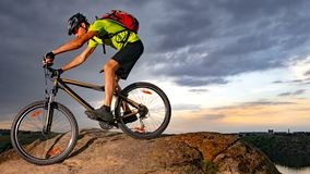 Cyclist Riding the Bike on Rocky Trail at Sunset. Extreme Sport and Enduro Biking Concept. Cyclist Riding the Bike on the Rocky Trail at Sunset. Extreme Sport royalty free stock photography