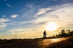 Cyclist riding Bike. Silhouette of cyclist riding Bike on road at sunset Royalty Free Stock Photos