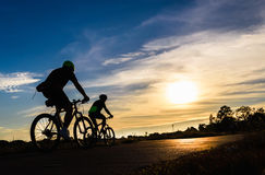 Cyclist riding Bike. Silhouette of cyclist riding Bike on road at sunset Stock Photo