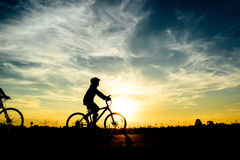 Cyclist riding Bike. Silhouette of cyclist riding Bike on road at sunset Royalty Free Stock Image