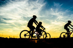 Cyclist riding Bike. Silhouette of cyclist riding Bike on road at sunset Royalty Free Stock Images