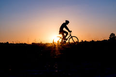 Cyclist riding Bike. Silhouette of cyclist riding Bike on road at sunset Royalty Free Stock Photography