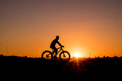Cyclist riding Bike. Silhouette of cyclist riding Bike on road at sunset Stock Photos