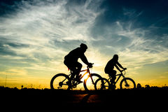 Cyclist riding Bike. Silhouette of cyclist riding Bike on road at sunset Stock Photography