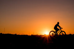 Cyclist riding Bike. Silhouette of cyclist riding Bike on road at sunset Royalty Free Stock Photo