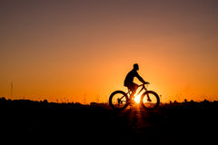 Cyclist riding Bike. Silhouette of cyclist riding Bike on road at sunset Stock Image