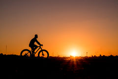 Cyclist riding Bike. Silhouette of cyclist riding Bike on road at sunset Stock Images