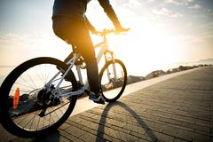 Cyclist riding bike in the coasts. Cyclist riding bike in the sunrise coast path stock image