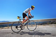Cyclist riding a bike uphill. A male cyclist riding a bike uphill along a road; clear summer day Stock Image