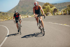 Cyclist riding bikes on open road Stock Photos