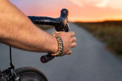 Cyclist riding a bycicle at sunset, pov view. royalty free stock image