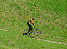 Cyclist Riding Down Hill on the Rear Wheel Royalty Free Stock Images