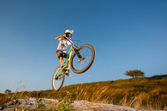 Cyclist riding downhill on mountain bike on the hill royalty free stock photos