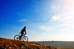 Cyclist riding his bike down on mountain trail. Beautiful sky and clouds on background Stock Photography
