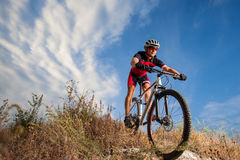 Cyclist riding his bike down on mountain trail Stock Image