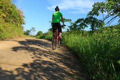 Cyclist riding mountain bike on country road Royalty Free Stock Images