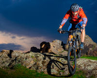 Cyclist Riding Mountain Bike Down Spring Rocky Hill at Beautiful Sunset. Extreme Sports and Adventure Concept. Royalty Free Stock Photo