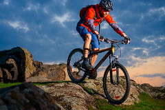 Cyclist Riding Mountain Bike Down Spring Rocky Hill at Beautiful Sunset. Extreme Sports and Adventure Concept. Stock Photography