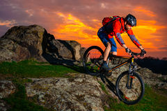Cyclist Riding Mountain Bike Down Spring Rocky Hill at Beautiful Sunset. Extreme Sports and Adventure Concept. Stock Photo