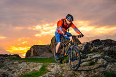 Cyclist Riding Mountain Bike Down Spring Rocky Hill at Beautiful Sunset. Extreme Sports and Adventure Concept. Royalty Free Stock Image