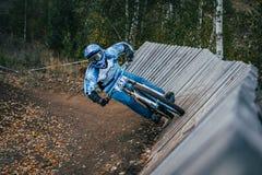 Cyclist riding a mountain bike downhill. Magnitogorsk, Russia - September 12, 2015: Cyclist riding a mountain bike downhill style during Urals Cup of downhill royalty free stock photos