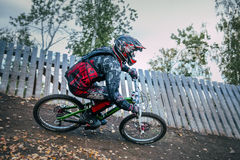 Cyclist riding a mountain bike downhill. Magnitogorsk, Russia - September 12, 2015: Cyclist riding a mountain bike downhill style during Urals Cup of downhill royalty free stock images