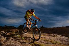 Cyclist Riding the Mountain Bike on Rocky Trail in the Evening. Extreme Sport and Enduro Biking Concept. stock images