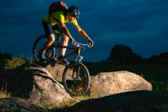 Cyclist Riding the Mountain Bike on Rocky Trail in the Evening. Extreme Sport and Enduro Biking Concept. Cyclist Riding the Mountain Bike on the Rocky Trail in royalty free stock photo