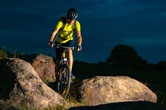 Cyclist Riding the Mountain Bike on Rocky Trail in the Evening. Extreme Sport and Enduro Biking Concept. stock photos