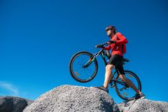 Cyclist riding mountain bike on the rocky trail at sunset, Extreme mountain bike sport athlete man riding outdoors lifestyle trail.  stock images