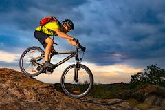 Cyclist Riding the Mountain Bike on Rocky Trail at Sunset. Extreme Sport and Enduro Biking Concept. stock photo