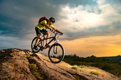 Cyclist Riding the Mountain Bike on Rocky Trail at Sunset. Extreme Sport and Enduro Biking Concept. Cyclist Riding the Mountain Bike on the Rocky Trail at royalty free stock image