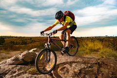 Cyclist Riding the Mountain Bike on Rocky Trail at Sunset. Extreme Sport and Enduro Biking Concept. stock photography