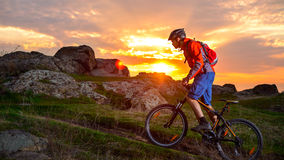Cyclist Riding Mountain Bike on the Spring Rocky Trail at Beautiful Sunset. Extreme Sports and Adventure Concept. Stock Photos