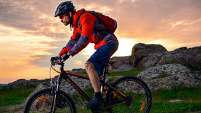 Cyclist Riding Mountain Bike on the Spring Rocky Trail at Beautiful Sunset. Extreme Sports and Adventure Concept. Royalty Free Stock Photo
