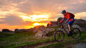 Cyclist Riding Mountain Bike on the Spring Rocky Trail at Beautiful Sunset. Extreme Sports and Adventure Concept. Stock Image